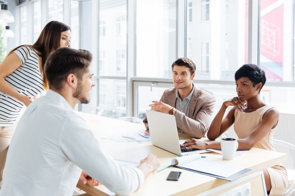 Successful young business people talking and working together in office